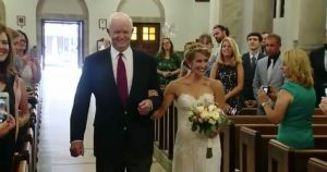 woman_walks_down_aisle_with_man_with_fathers_heart_featured